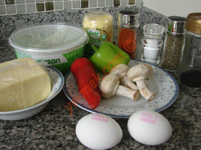 İtalyan Omlet (Dolmalık Biberli, Mantarlı ve Çörek Otlu) İçin Gerekli Malzemeler :  <ul> <li>2 yumurta</li> <li>1/2 adet dolmalık biber</li> <li>1 adet kırmızı biber</li> <li>3-4 adet Mantar</li> <li>Çörek Otu</li> <li>Az Yoğurt</li> <li>Tuz</li> <li>Kekik</li> <li>Kırmızı toz biber</li> <li>Tereyağı</li> <li>Kaşar</li> </ul>
