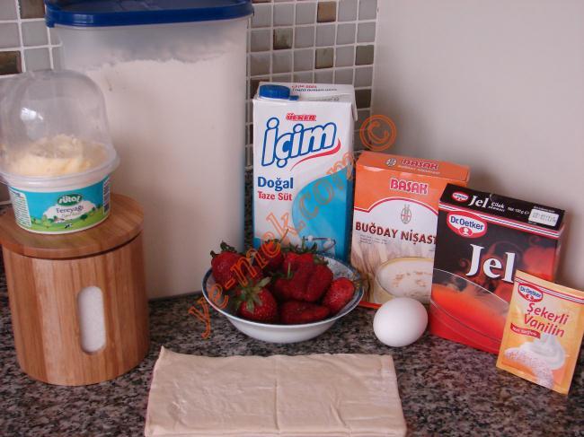 Çilekli Milföy Pasta İçin Gerekli Malzemeler :  <ul> <li>2 adet bütün milföy hamuru</li> <li>Yarım kilo çilek</li> <li>1 paket çilek jölesi</li> <li><strong>Pasta Kreması için:</strong></li> <li>2 su bardağı süt</li> <li>2 yemek kaşığı un</li> <li>1 yemek kaşığı nişasta</li> <li>2 yemek kaşığı toz şeker</li> <li>1 adet yumurta</li> <li>1 yemek kaşığı tereyağı</li> <li>1 çay kaşığı vanilya</li> </ul>
