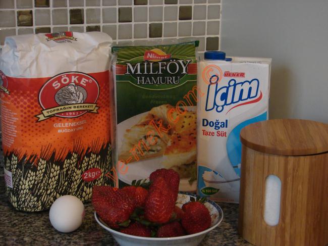 Çilekli Milföy Tart İçin Gerekli Malzemeler :  <ul>  <li>4 tane milföy hamuru</li> <li>İstediğiniz miktarda çilek</li>  <li><strong>Krema İçin:</li></strong>          <li>2 su bardağı süt</li> <li>Yarım su bardağı toz şeker</li> <li>4 yemek kaşığı un</li> <li>1 adet yumurta sarısı</li>          <li><strong>Üzeri İçin:</strong></li>         <li>Pudra şekeri</li> </ul>