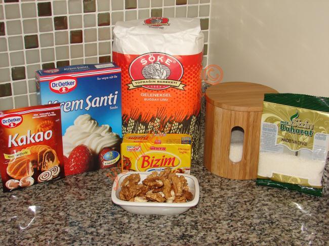 Saray Lokumu ( Paşa Lokumu) İçin Gerekli Malzemeler :  <ul> <li>1 litre süt</li> <li>1 su bardağı un</li> <li>2 su bardağı toz şeker</li> <li>1 paket kakao (25 gr)</li> <li>125 gr margarin</li> <li>200 gr hindistan cevizi</li> <li>2 paket krem şanti</li>         <li>1 su bardağı süt</li> <li>Az dövülmüş ceviz ya da fındık</li> </ul>