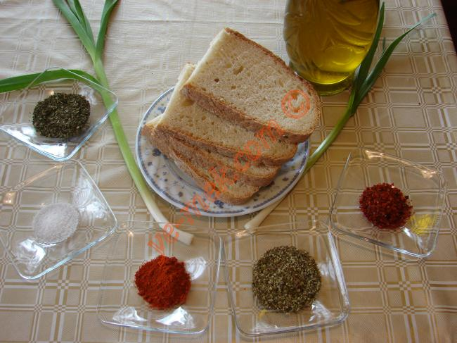 Zeytinyağlı Çeşnili Fırında Ekmek Dilimleri İçin Gerekli Malzemeler :  <ul> <li>6 dilim ekmek</li> <li>Zeytinyağı</li> <li>Kırmızı toz biber</li> <li>Nane</li> <li>Kekik</li> <li>Taze sarımsak</li> <li>Tuz</li> <li>Kırmızı pulbiber</li> </ul>