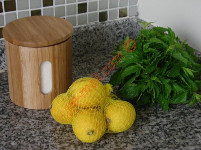 Naneli Limonata İçin Gerekli Malzemeler :  <ul> <li>6 adet orta büyüklükte limon</li> <li>1/2 demet nane</li> <li>2 su bardağı toz şeker</li> <li>5-6 su bardağı su</li> <li><strong>Süslemek İçin:</strong></li> <li>Nane yaprakları</li> <li>Buz Parçaları</li> <li>Limon dilimleri</li> </ul>