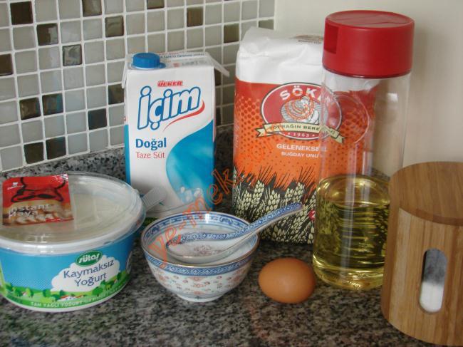 Saçaklı (Sakallı) Poğaça İçin Gerekli Malzemeler :  <ul> <li>1 su bardağı ılık süt</li> <li>1/2 su bardağı yoğurt</li> <li>1/2 su bardağı sıvıyağ</li> <li>1 adet yumurta</li> <li>1 yemek kaşığı toz şeker</li> <li>1/2 tatlı kaşığı tuz</li> <li>1 yemek kaşığı instant kuru maya</li> <li>4,5 su bardağı un (azar azar koyun )</li> <li>Labne peynir</li> <li>Beyaz peynir</li> <li>Maydanoz</li> <li>Kaşar peynir</li>  <li><strong>Üzeri İçin:</strong></li>  <li>Yumurta sarısı</li> </ul>