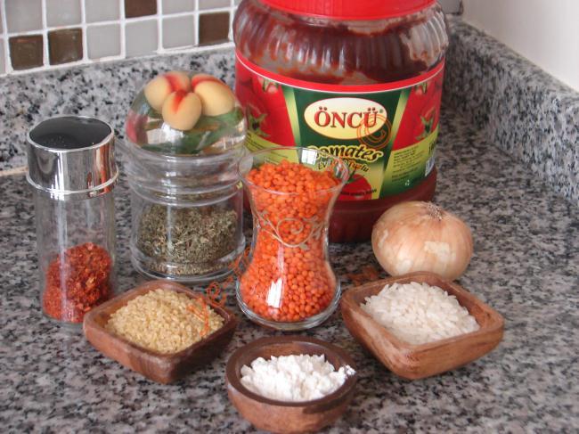 Kolay Ezogelin Çorbası İçin Gerekli Malzemeler :  <ul> <li>1 çay bardağı kırmızı mercimek</li> <li>2 yemek kaşığı bulgur</li> <li>2 yemek kaşığı pirinç</li> <li>1 adet soğan</li> <li>1 yemek kaşığı tereyağı</li> <li>1 yemek kaşığı un</li> <li>1,5 yemek kaşığı domates salçası</li> <li>5-5,5 su bardağı su</li> <li>2-3 tatlı kaşığı nane</li> <li>1 tatlı kaşığı pulbiber</li> <li>Tuz</li> <li>Karabiber</li> <li><strong>Üzeri İçin:</strong></li> <li>Nane</li> <li>Pulbiber</li> </ul>
