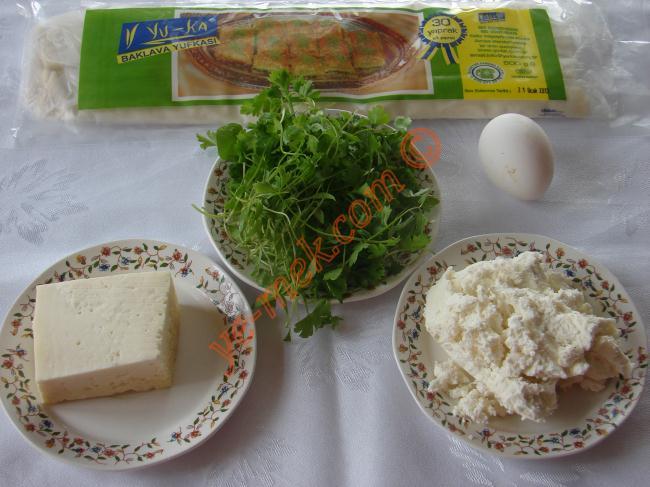 Baklavalık Yufkadan Börek İçin Gerekli Malzemeler :  <ul> <li>8 adet hazır baklavalık yufka</li> <li>4 yemek kaşığı rendelenmiş mihaliç peynir</li> <li>100 gr beyaz peynir</li> <li>4 yemek kaşığı tereyağı</li> <li>2 tutam maydanoz</li> <li><strong>Üzeri İçin:</strong></li>  <li>Susam</li> <li>1 adet yumurta sarısı</li> </ul>