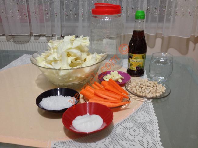 Beyaz Lahana Turşusu İçin Gerekli Malzemeler :  <ul> <li>1 adet küçük boy lahana</li> <li>6 adet havuç</li> <li>1 baş sarımsak</li> <li>1 avuç nohut</li> <li>2 yemek kaşığı kaya tuzu</li> <li>2 tatlı kaşığı toz şeker</li> <li>1 su bardağı üzüm sirkesi</li> <li>Kavanozu dolduracak kadar içme suyu</li> <li>Doğranmış lahanayı ovmak için 1,5-2 yemek kaşığı tuz</li> </ul>Beyaz lahana turşusu yapımında; öncelikle 1 adet küçük boy lahanayı iri iri doğrayın. Daha az yer kaplaması için tuzla güzelce ovun. Akabinde yumuşayan lahanaları yıkayıp, süzün. 1 baş sarımsağı dişlerine ayırıp, kabuklarını soyun. 6 adet havucun da kabuğunu soyup, uzunlamasına kesin.