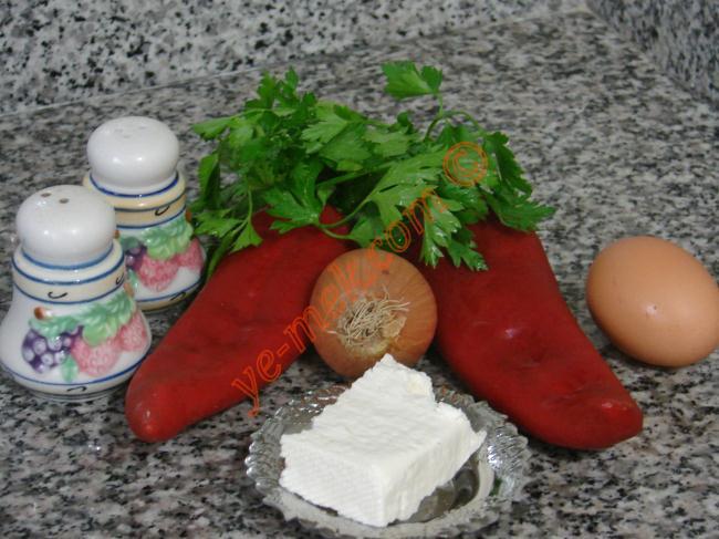 Kırmızı Biberli Mücver İçin Gerekli Malzemeler :  <ul> <li>2 adet orta boy kırmızı biber</li> <li>2 adet yumurta</li> <li>50 gr beyaz peynir</li> <li>2 tutam maydanoz</li> <li>1 adet küçük boy soğan</li> <li>2 yemek kaşığı dolusu un</li> <li>1 çay kaşığı kabartma tozu (isteğe göre)</li> <li>Tuz</li> <li>Karabiber</li> <li>Kızartmak için sıvıyağ</li> </ul>