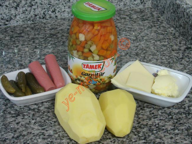 Pofuduk Kumpir İçin Gerekli Malzemeler :  <ul> <li>2 adet orta boy patates</li> <li>5 yemek kaşığı garnitür</li> <li>1 yemek kaşığı tereyağı</li> <li>Küçük bir kase rendelenmiş kaşar peynir</li> <li>Tuz</li> <li>Karabiber</li> <li><strong>Üzeri İçin:</strong></li> <li>6 adet kornişon turşu</li> <li>3 adet küçük boy sosis</li> <li>Ketçap</li> <li>Mayonez</li> </ul>