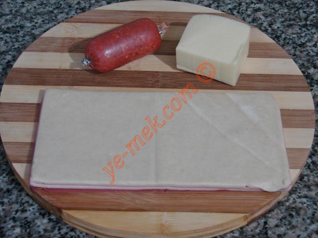 Rüzgar Gülü Böreği İçin Gerekli Malzemeler :  <ul> <li>4 adet milföy</li> <li>4 dilim kaşar peynir</li> <li>4 parça sucuk</li> <li>Tereyağı</li> <li><strong>Üzeri İçin:</strong></li>  <li>Yumurta sarısı</li> </ul>