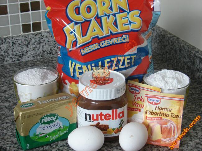 Çikolatalı Mısır Gevrekli Kurabiye İçin Gerekli Malzemeler :  <ul> <li>250 gr tereyağı (oda sıcaklığında)</li> <li>2 adet yumurta</li> <li>1 su bardağı pudra şekeri</li> <li>2,5 su bardağı nişasta</li> <li>1 paket kabartma tozu</li> <li>1 paket vanilya</li> <li>2,5 su bardağı un</li> <li><strong>Bulamak İçin:</strong> <li>Mısır gevreği</li> <li>Bir orta boy kavanoz nutella ya da çokokrem</li> <li>3 yemek kaşığı sıvıyağ</li> </ul>