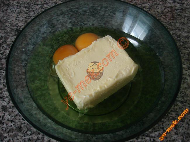 Çikolatalı mısır gevrekli kurabiye için; derin bir kap içine 2 adet yumurta kırın. Üzerine 250 gr tereyağı ekleyin.