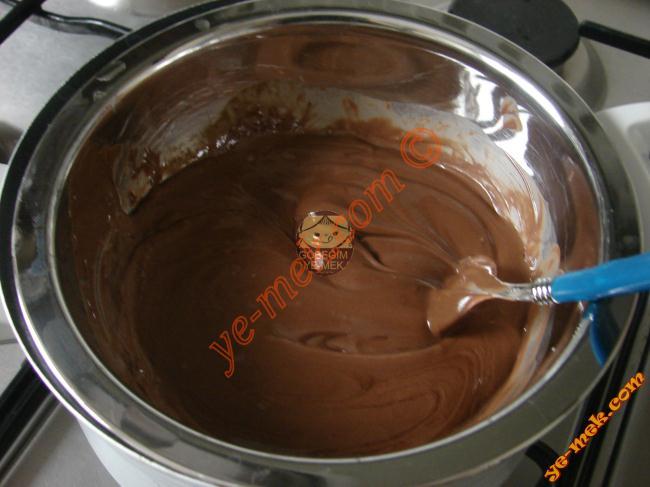 Diğer tarafta 1 adet orta boy kavanoz nutellayı ısıya dayanıklı bir kaba alıp, benmari usulü eritin. Benmari Yöntemi; Büyük bir tencere içine su eklenir, kaynayınca altı kısılır. İçine daha küçük bir tencere konulur vebu tencerenin içine su temas ettirmeden eritilecek malzeme konulur. Eriyen çikolatayı ocaktan alın. Çikolatanın koyuluğunu açmak için üzerine 3 yemek kaşığı sıvı yağ ekleyip, karıştırın. Başka bir kaba da mısır gevreğini elinizle parçalayarak koyun.