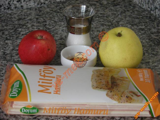 Elmalı Örgü Milföy İçin Gerekli Malzemeler :  <ul> <li>6 adet kare milföy hamuru</li> <li>2 adet orta boy elma</li> <li>3 yemek kaşığı toz şeker</li> <li>1 çay kaşığı tarçın</li> <li><strong>Üzeri İçin:</strong></li> <li>Pudra şekeri</li> </ul>