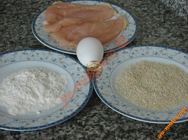 Susamlı Çıtır Tavuk İçin Gerekli Malzemeler :  <ul> <li>2 dilim tavuk göğüsü</li> <li>80 gr kadar susam</li> <li>1 adet yumurta</li> <li>2-3 yemek kaşığı un</li> <li>1/2 çay kaşığı köri</li> <li>1 yemek kaşığı soya sosu</li> <li>Çok az tuz</li> <li>Kızartmak için sıvıyağ</li> </ul>