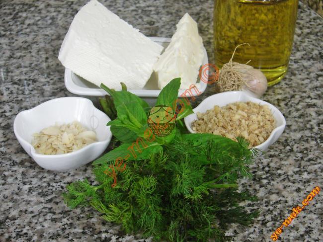 Girit Ezmesi İçin Gerekli Malzemeler :  <ul> <li>150 gr tam yağlı peynir</li> <li>50 gr ezine peynir ya da lor peynir</li> <li>1 diş sarımsak</li> <li>5 yemek kaşığı dövülmüş ceviz içi</li> <li>2 yemek kaşığı file badem</li> <li>5 yemek kaşığı zeytinyağı</li> <li>1 tutam taze nane</li> <li>1 tutam dereotu</li> <li>Kırmızı toz biber</li> </ul>