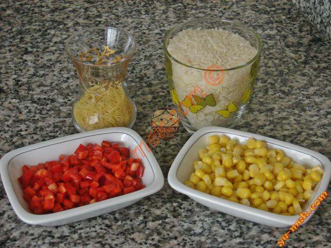 Kırmızı Biberli  Mısırlı Pilav İçin Gerekli Malzemeler :  <ul> <li>1 su bardağı pilavlık pirinç</li> <li>3 yemek kaşığı tel şehriye</li>         <li>1 adet büyük boy kırmızı biber</li>         <li>Küçük bir kase konserve mısır</li> <li>1,5 yemek kaşığı tereyağı</li> <li>2 su bardağı sıcak su</li> <li>1 adet kesme şeker</li>         <li>2 tutam kuru nane</li>         <li>Karabiber</li> <li>Tuz</li> </ul>