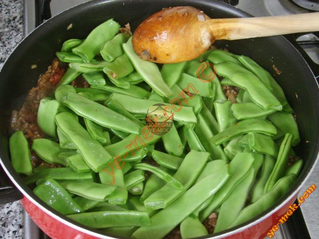 Çevirdikten sonra fasulyeleri ekleyip, karıştırın. Kısık ateşte fasulyeler yumuşayıp, suyunu çekene kadar pişirin. Kısık ateşte fasulyeler yumuşayıp, suyunu çekene kadar pişirin.