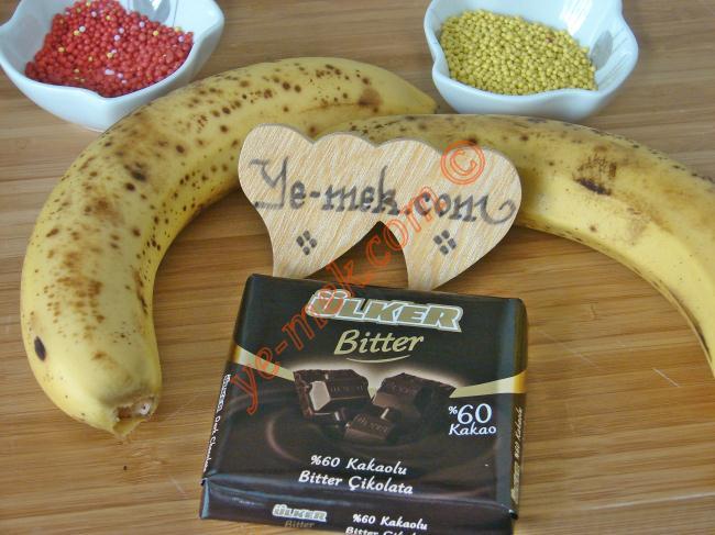 Çikolatalı Muz Dilimleri İçin Gerekli Malzemeler :  <ul> <li>2 adet orta boy muz</li> <li>80 gr bitter çikolata ya da sütlü çikolata</li> <li>2 adet tahta şiş</li>  <li><strong>Üzeri İçin:</strong></li>  <li>Renkli şeker süsleri</li> <li>Yeşil dövülmüş fıstık</li> </ul>