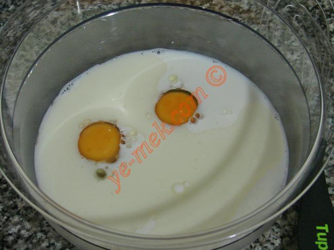 Derin bir kaba 2 adet yumurta kırın. Üzerine 3 yemek kaşığı sıvıyağ ve 1 su bardağı süt ekleyip, iyice çırpın.