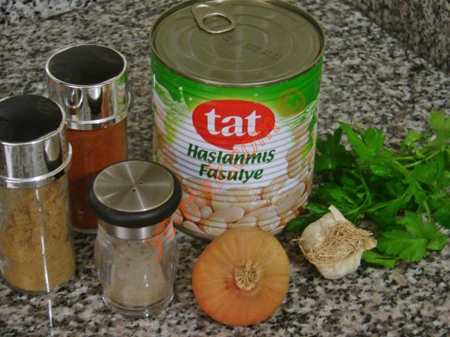 Fasulye Ezmesi İçin Gerekli Malzemeler :  <ul>  <li>1 su bardağı haşlanmış kuru fasulye</li> <li>1 adet taze soğan</li> <li>1 diş sarımsak</li> <li>2 yemek kaşığı zeytinyağı</li> <li>1/2 çay kaşığı pul biber ya da kırmızı toz biber</li>         <li>1/2 çay kaşığı kimyon</li>         <li>1/2 çay kaşığı karabiber</li> <li>Tuz</li>  <li><strong>Üzeri İçin</strong></li>  <li>Maydanoz</li> </ul>