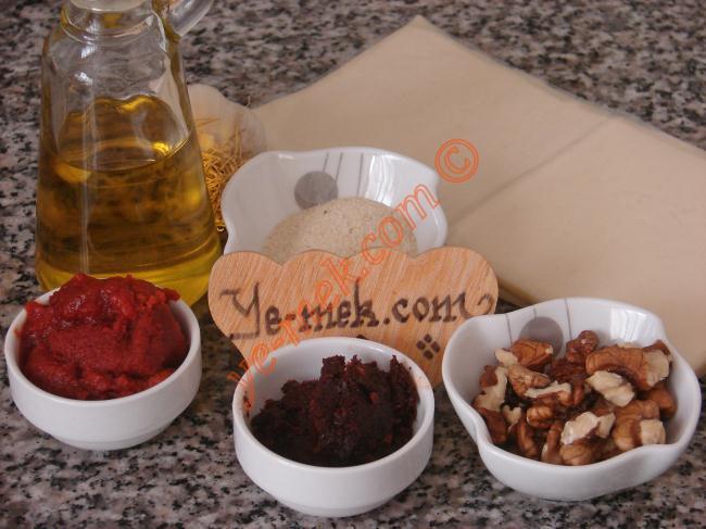 Çemenli Mini Milföyler İçin Gerekli Malzemeler :  <ul> <li>3 adet dikdörtgen milföy hamuru</li> <li>2 yemek kaşığı domates salçası</li> <li>1 yemek kaşığı biber salçası</li> <li>1 diş sarımsak</li>         <li>2-3 yemek kaşığı dövülmüş ceviz</li>         <li>1-2 yemek kaşığı galeta unu</li>         <li>3 yemek kaşığı zeytinyağı</li>         <li>Kimyon</li>         <li>Nane</li>         <li>Kırmızı pulbiber</li>  <li><strong>Üzeri İçin:</strong> <ul> <li>Yumurta sarısı</li> </ul> </li> </ul>