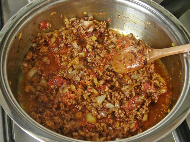 Derin bir tencereye 3 yeme kaşığı zeytinyağ koyun. Üzerine ince ince doğranmış soğanı, sarımsağı ve kıymayı ekleyin. Sürekli karıştırarak, 5 dakika kadar pişirin.