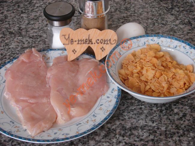 Mısır Gevrekli Tavuk Şinitzel İçin Gerekli Malzemeler :  <ul> <li>2 dilim tavuk fileto</li> <li>1 adet yumurta</li> <li>1 su bardağı mısır gevreği</li> <li>Tuz</li> <li>Kırmızı toz biber</li>         <li>Kimyon</li>         <li>Az miktar köri</li> <li><strong>Kızartmak İçin:</strong></li> <li>1/2 su bardağı sıvıyağ</li>  </ul>