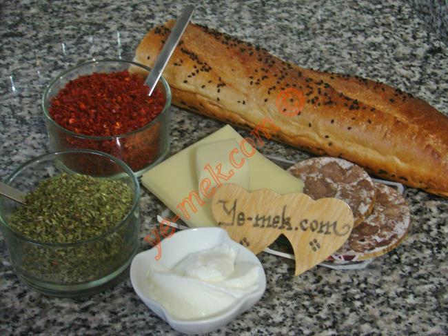 Kavurmalı Ekmek Pizzası İçin Gerekli Malzemeler :  <ul> <li>1 adet baston ekmek</li> <li>4 adet büyük dilim kaşar peynir</li> <li>1 dilim kavurma</li> <li>1/2 yemek kaşığı yoğurt</li>         <li>Kırmızı pul biber</li>         <li>Kekik</li> </ul>