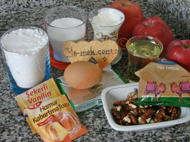 Elmalı Düğme Kurabiye İçin Gerekli Malzemeler :  <ul> <li>125 gr tereyağı (Oda sıcaklığında)</li>         <li>1 çay bardağı sıvı yağ</li>         <li>1 çay bardağı yoğurt</li>         <li>1 adet yumurta</li>         <li>1,5 çay bardağı toz şeker</li>         <li>1 su bardağı buğday nişastası</li>         <li>1/2 paket kabartma tozu</li>         <li>1 paket vanilya</li>         <li>3 su bardağı un</li> <li><strong>İç Harcı İçin:</strong></li> <li>4 adet büyük boy elma</li>         <li>4 yemek kaşığı toz şeker</li>         <li>1 tatlı kaşığı tarçın</li>         <li>1 çay bardağı dövülmüş ceviz</li>   </ul>