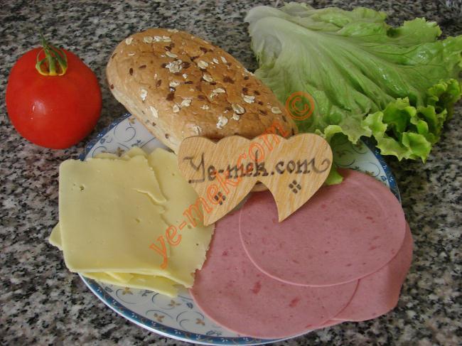 Jambonlu Sandviç İçin Gerekli Malzemeler :  <ul> <li>1 adet sandviç ekmek</li>         <li>4 dilim hindi jambon</li>         <li>4 dilim kaşar peynir</li> <li>2 adet marul yaprağı</li> <li>3-4 dilim domates</li> </ul>