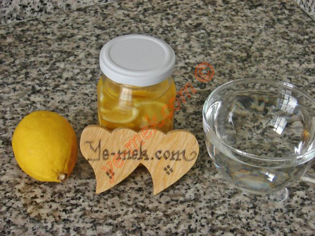 Zencefilli Limon Çayı İçin Gerekli Malzemeler :  <ul> <li>1 çay fincanı sıcak su</li> <li>1 dilim limon</li> <li>Zencefilli limonlu bal karışımı</li> </ul>