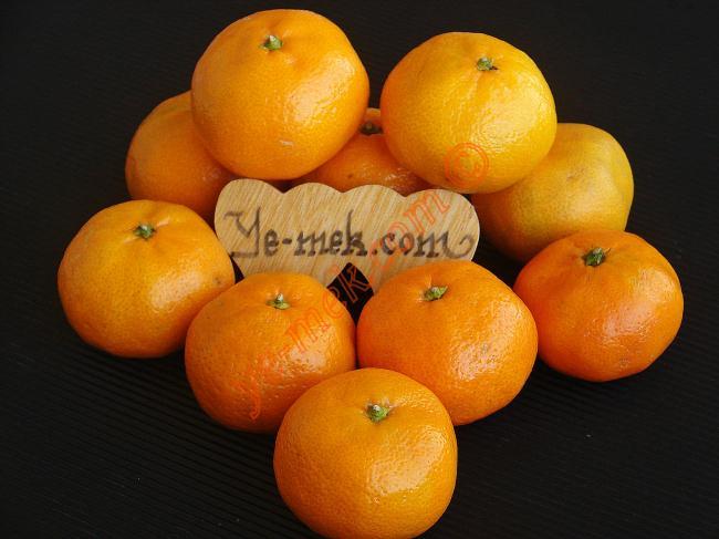"""Mandalina, özellikle kış aylarında çok tüketilen bir turunçgildir. Tatlı, sulu ve hoş kokulu bir meyvedir. Ilıman iklimlerde yetişir. Çekirdekli ve çekirdeksiz olabilir.    Mandalina zengin bir vitamin kaynağıdır. A, B ve C vitamini deposudur. Günde 2-3 adet tüketilmesi önemlidir.  Mandalina sahip olduğu vitaminlerin yanında aynı zamanda zengin bir mineral deposudur. Özellikle magnezyum, sodyum, fosfor, kalsiyum, potasyum ve demir minerallerini içerir. Kabuğunda ise """"P Vitamini"""" bolca bulunur.     Mandalinanın Faydaları   Soğuk algınlığı, grip, nezle hastalıklarını atlatmak için tüketilmesinde fayda vardır. Antioksidan kaynağıdır. Bolca antioksidan içerir.  Bağışıklık sistemini geliştirir. Damar sertliğini azaltır. Kalp ve damar hastalıklarına karşı vücudu güçlendirir. Kanı temizler.  Hepatit hastalığına iyi gelir.  Kolesterole iyi gelir.Yüksek tansiyonu düşürür. Sinirleri yatıştırır. Susuzluğu giderir.     Sindirim sistemini düzenler. Bağırsaklara faydası vardır. Kabızlığı giderir.  Vücudun savunmasını güçlendirir ve hücrelerin erken yaşlanmasını önler.     Mandalinanın Kilo Vermeye Faydası ve Tok Tutucu Etkisi  Yoğun lif ve vitamin kaynağı olduğu için vücudun direncini arttırır. Metabolizmayı hızlandırdığı için kilo verme sürecini destekler.   Mandalinanın Kilo Vermeye Faydası ve Tok Tutucu Etkisi  Diyet programlarında, vücuda enerji vermesi ve kalori yakımını hızlandırdığı için tercih edilir. Açlığı giderir. Diyet programlarında ara öğün olarak tüketebilirsiniz.  Mandalinayı soyduğunuz zaman içindeki beyaz lifleri temizlemeden tüketmelisiniz. Beyaz lifler tokluk hissini arttırmada faydalıdır.  Mandalina İle Neler Yapılır?  Taze meyve olarak tüketilebileceği gibi reçeli de yapılabilir.  Kabukları ince ince rendelenip, kek ve tatlı tariflerinde hem koku hem de esans vermesi açısından kullanabilir. Arzu ederseniz limonata yapımında dahi bu kabuklardan yararlanabilirsiniz."""