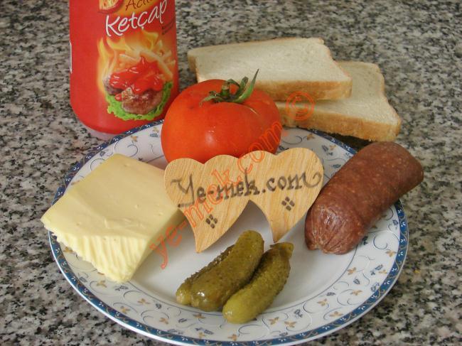 Yengen Tostu İçin Gerekli Malzemeler :  <ul> <li>2 dilim tost ekmeği</li> <li>4 dilim sucuk</li> <li>4 dilim kaşar peynir</li>         <li>2 adet minik kornişon turşu</li>         <li>Domates</li>         <li>Ketçap</li> </ul>