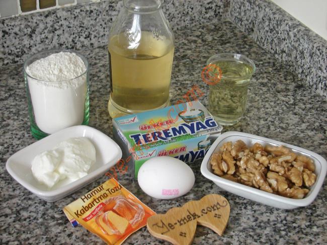 Bülbül Konağı Tatlısı İçin Gerekli Malzemeler :  <ul> <li><strong>Hamuru İçin:</strong></li> <li>1 adet yumurta</li> <li>1 paket margarin</li> <li>1,5 yemek kaşığı yoğurt</li> <li>1 yemek kaşığı elma sirkesi</li> <li>1 çay bardağı sıvıyağ</li> <li>1 paket kabartma tozu</li>         <li>1 kase ceviz</li> <li>Yaklaşık 3,5 su bardağı un</li> <li><strong>Şerbeti İçin:</strong></li> <li>4 su bardağı su</li> <li>4 su bardağı toz şeker</li> <li>3 diş limon tuzu</li> </ul>