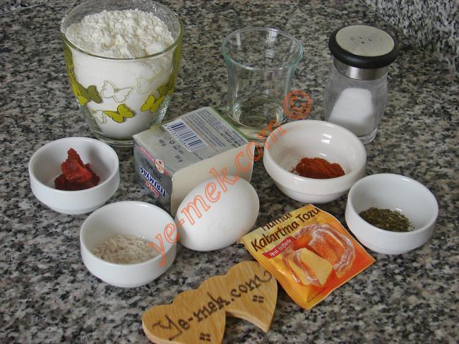 Salçalı Kurabiye İçin Gerekli Malzemeler :  <ul> <li>100 gr margarin (oda sıcaklığında)</li> <li>1 adet yumurta</li> <li>1/4 çay bardağı elma sirkesi</li>         <li>1 tatlı kaşığı domates salçası</li> <li>1 çay kaşığı (silme) tuz</li>         <li>1/2 paket kabartma tozu</li> <li>1/2 tatlı kaşığı kırmızı toz biber</li> <li>1/2 tatlı kaşığı nane</li> <li>1/2 tatlı kaşığı mahlep</li>         <li>2 su bardağı kadar un</li> <li><strong>Üzeri İçin:</strong></li>  <li>Yumurta sarısı</li>         <li>Çörek otu</li> </ul>
