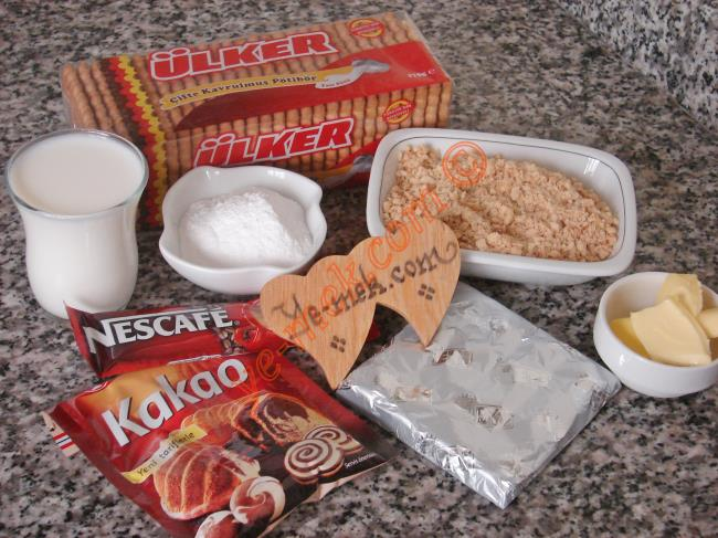 Kakaolu Bisküvi Topları İçin Gerekli Malzemeler :  <ul> <li>1,5 paket çifte kavrulmuş pötibör bisküvi</li> <li>3 yemek kaşığı pudra şekeri</li> <li>1 çay bardağı süt</li> <li>1 paket tek kullanımlık neskafe üçü bir arada</li> <li>1,5 yemek kaşığı tereyağı (oda sıcaklığında)</li>         <li>1,5 yemek kaşığı kakao</li>         <li>1/4 su bardağı az dövülmüş fındık</li> <li><strong>Üzeri İçin:</strong></li>         <li>30 gr bitter  çikolata</li> <li>Renkli şeker süsleri</li> </ul>