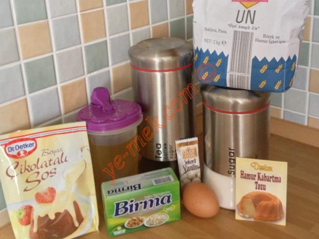 İngiliz Kurabiyesi İçin Gerekli Malzemeler :  <ul> <li>125 gr margarin (oda sıcaklığında)</li> <li>1 çay bardağı zeytinyağı</li> <li>1 su bardağı toz şeker</li>         <li>1 adet yumurta</li> <li>2 yemek kaşığı siyah çay tozu</li> <li>1 paket kabartma tozu</li> <li>1 paket vanilya</li> <li>Yaklaşık 3 su bardağı un</li> <li><strong>Üzeri İçin:</strong></li> <li>1 paket beyaz çikolatalı sos</li>  </ul>