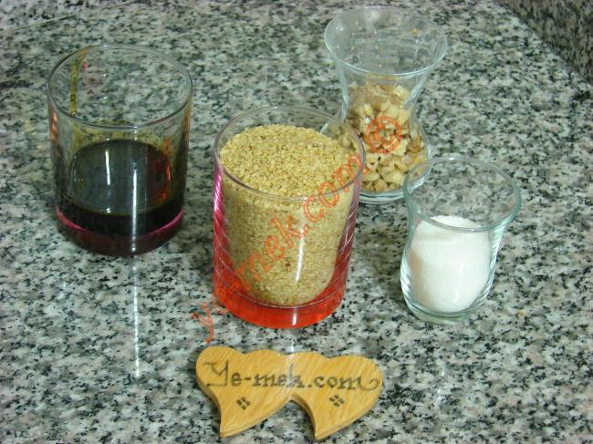Küncülü Akıt İçin Gerekli Malzemeler :  <ul> <li>1 su bardağı kavrulmamış susam</li> <li>1/2 çay bardağı kırılmış ceviz</li> <li>1/4 su bardağı pekmez</li>         <li>1/2 çay bardağı toz şeker (küçük çay bardağı)</li> </ul>