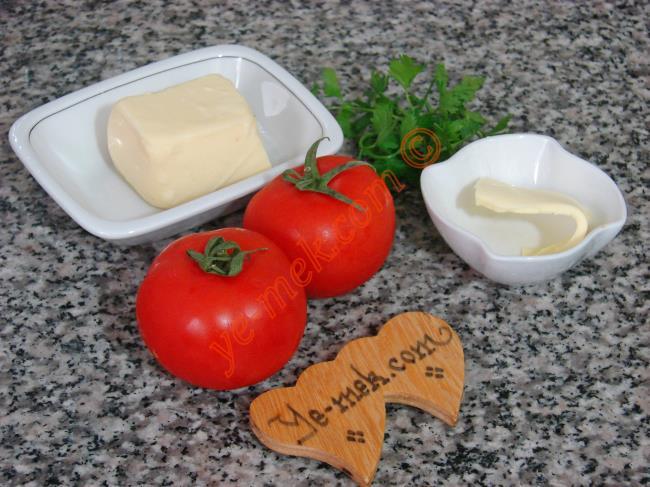 Fırında Kahvaltılık Domates Dilimleri İçin Gerekli Malzemeler :  <ul> <li>2 adet orta boy domates </li> <li>1/2 yemek kaşığı tereyağı</li> <li>Rendelenmiş kaşar peynir</li>         <li>1 tutam maydanoz</li> </ul>