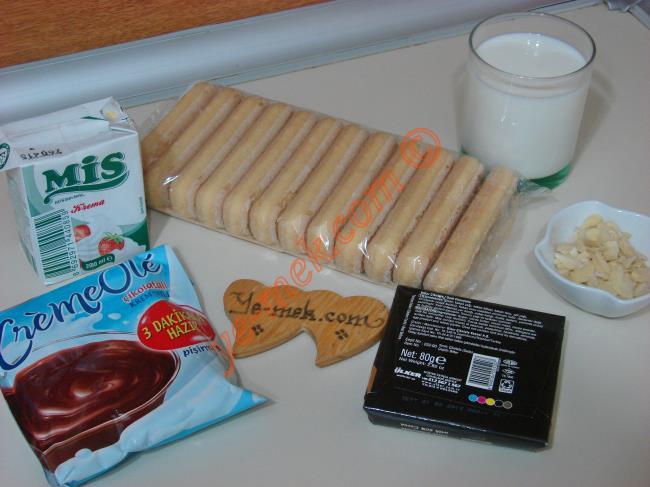 Çikolatalı Kedi Dili Ekler Pasta İçin Gerekli Malzemeler :  <ul> <li>1 paket kedi dili bisküvi</li>         <li>1 paket çikolatalı crem ole</li>         <li>1,5 su bardağından biraz fazla süt</li>          <li>File badem ya da dövülmüş fındık</li> <li><strong>Üzeri İçin:</strong></li> <li>2,5 yemek kaşığı süt kreması</li>         <li>80 gr bitter ya da sütlü çikolata</li> </ul>