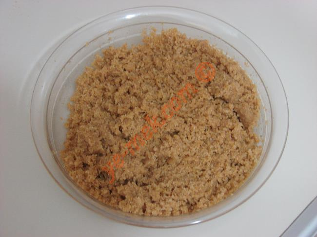Erimiş tereyağı ufalanmış bisküvilerin üzerine döküp, birbirlerine iyice yedirin.  Hazırladığınız bisküvili karışımı silikon muffin kalıpları içine yaklaşık 2 yemek kaşığı kadar paylaştırın.