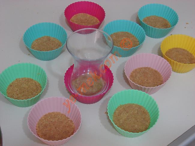 Bisküvilerin üzerine çay bardağı ile bastırın. Kenardaki bisküvi tanelerini kaşıkla düzeltin.
