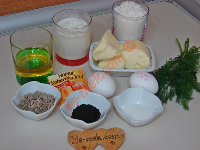 Dereotlu Kurabiye İçin Gerekli Malzemeler :  <ul> <li>125 gr tereyağı (Oda sıcaklığında)</li> <li>1/2 su bardağı zeytinyağı</li> <li>6 yemek kaşığı yoğurt</li>         <li>2 yumurta akı (sarısı üzeri için)</li> <li>1 tatlı kaşığı tuz</li> <li>1 tatlı kaşığı toz şeker</li> <li>1 paket kabartma tozu</li> <li>Yarım demetten biraz fazla dereotu</li> <li>3,5 su bardağı un</li> <li><strong>Üzeri İçin:</strong></li> <li>Yumurta sarısı</li> <li>Ay çekirdeği, çörek otu ya da susam</li> </ul>