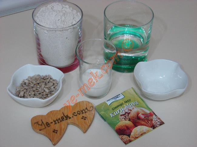 Ev Yapımı Çavdar Ekmeği İçin Gerekli Malzemeler :  <ul> <li>1/2 çay bardağı ılık süt (Küçük boy)</li> <li>1 su bardağı ılık su (200 ml)</li> <li>1/2 çay kaşığı tuz</li> <li>1 paket 7 gramlık kuru maya</li>         <li>5 yemek kaşığı ayçekirdeği</li>         <li>3-3,5 su bardağı kadar un</li> <li><strong>Üzeri İçin:</strong></li> <li>2 yemek kaşığı su</li> <li>2 yemek kaşığı zeytinyağı</li> </ul>