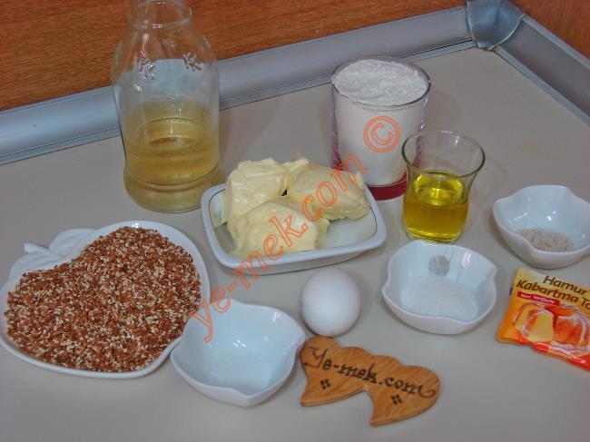 Ev Yapımı Kandil Simidi İçin Gerekli Malzemeler :  <ul> <li>125 gr tereyağı (Oda Isısında)</li> <li>1 yumurta sarısı</li> <li>1 yemek kaşığı sirke</li> <li>1 yemek kaşığı toz şeker</li> <li>1 çay kaşığı tuz</li>         <li>1/2 çay bardağı zeytinyağı (klasik çay bardağı)</li>         <li>1 çay kaşığı mahlep</li>         <li>1/2 paket kabartma tozu</li>         <li>3 su bardağı kadar un</li>         <li><strong> Üzeri İçin :</strong> </li> <li>1 adet yumurta akı</li>         <li>Kavrulmuş susam</li> </ul>