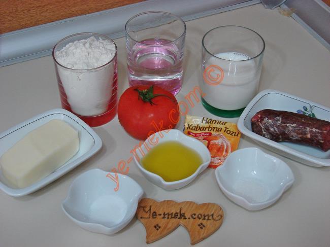 Mayasız İçli Pişi İçin Gerekli Malzemeler :  <ul> <li>1/2 su bardağı süt</li> <li>1/2 su bardağı su</li> <li>4 yemek kaşığı zeytinyağı</li>         <li>1 çay kaşığı toz şeker</li>         <li>1 tatlı kaşığı tuz</li> <li>1 paket kabartma tozu</li> <li>2,5-3 su bardağı kadar un</li> <li><strong>İçi İçin:</strong></li> <li>Domates</li> <li>Sucuk</li>          <li>Kaşar peynir</li> </ul>