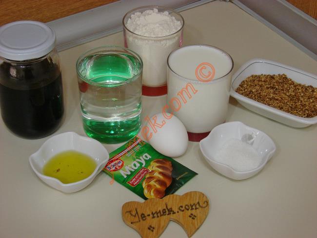 Zeytinli İçli Simit İçin Gerekli Malzemeler :  <ul> <li>1 su bardağı ılık su</li> <li>1 su bardağı ılık süt</li> <li>1 adet küçük boy yumurta</li>         <li>1 yemek kaşığı toz maya</li> <li>1 yemek kaşığı toz şeker</li> <li>1 tatlı kaşığı tuz</li>         <li>2 yemek kaşığı zeytinyağı</li>         <li>5,5-6 su bardağı kadar un</li>         <li><strong> İçi İçin :</strong> </li>         <li>Zeytin</li>         <li><strong> Üzeri İçin :</strong> </li> <li>1 büyük çay bardağı su</li>         <li>5 yemek kaşığı pekmez</li>         <li>Kavrulmuş susam</li> </ul>