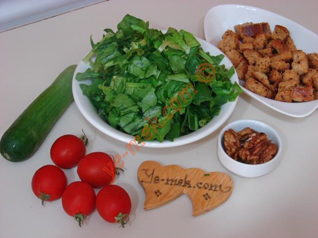 Krutonlu Ispanak Salatası İçin Gerekli Malzemeler :  <ul>         <li>150 gr ıspanak </li>         <li>1 adet salatalık </li>         <li>5 adet çeri domatesi</li>         <li>6 adet ceviz içi </li> <li>4 dilim ekmek </li> <li>Yarım yemek kaşığı tereyağ</li> <li>Yarım yemek kaşığı zeytinyağı</li> <li>Kırmızı Toz Biber</li>         <li>Limon suyu ya da nar ekşisi </li> </ul>