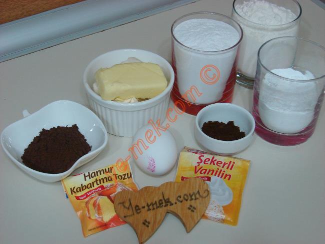 Kahve Çekirdeği Kurabiyesi İçin Gerekli Malzemeler :  <ul> <li>125 gr tereyağı (oda sıcaklığında)</li> <li>1 adet yumurta</li>         <li>1 su bardağı pudra şekeri</li>         <li>Yarım su bardağı nişasta</li> <li>2,5 yemek kaşığı kakao</li> <li>1,5 tatlı kaşığı türk kahvesi</li> <li>1 çay kaşığı kabartma tozu</li>         <li>1 tatlı kaşığı vanilya</li>         <li>2 su bardağına yakın un</li>  </ul>