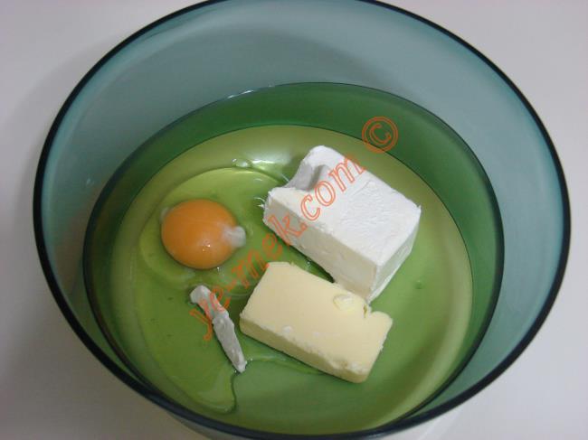 Derin bir kaba 125 gr tereyağı koyun. Üzerine 1 adet yumurta kırın.